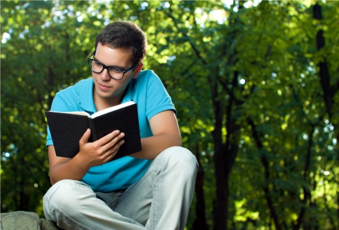 young man reading book in the park