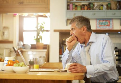 Man yawning at kitchen table with laptop.