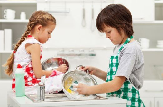 Grumpy kids doing home chores on parents order - washing dishes