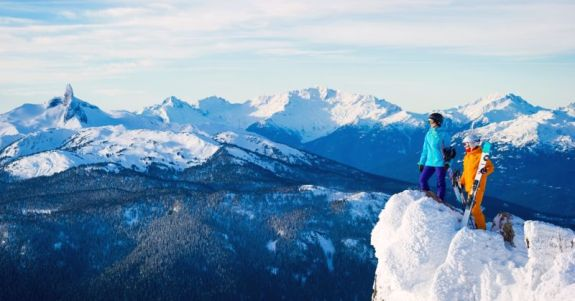 Female skiers and rider checking out the stunning alpine views from Whistler peak