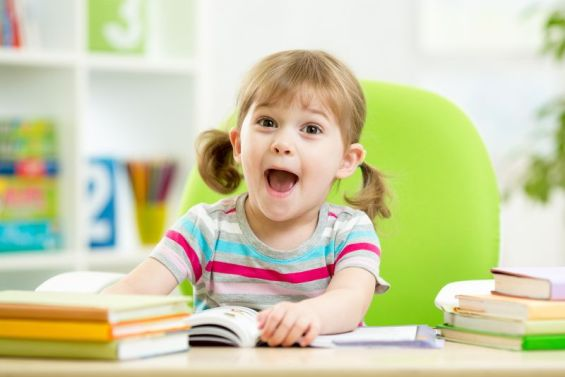 Happy kid reading book at table in nursery