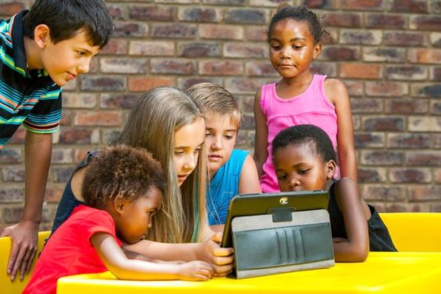 Multiracial group of children looking at tablet outdoors.