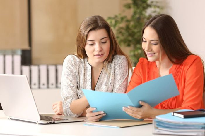 Businesswomen consulting a report together