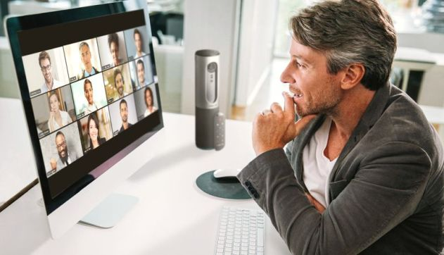 man at his desk interacting with a zoom meeting showing on a lar
